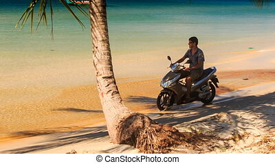 Guy on Scooter starts to Drive from Palm Shadow on Beach -...
