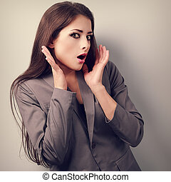Stressed surprising business woman in suit with hand near...