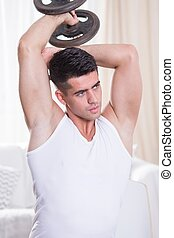 Exercising triceps with dumbbell - Young active man...