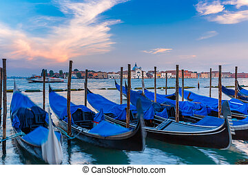 Gondolas at twilight in Venice lagoon, Italia - Gondolas...