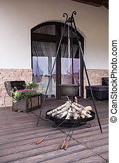 Cast-iron kettle on terrace - Cast-iron kettle and fireplace...