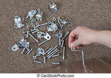 Furniture assembly hand tool, hex wrench screw screwed into...