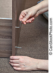 Woodworker assembling furniture at home using hex wrench,...