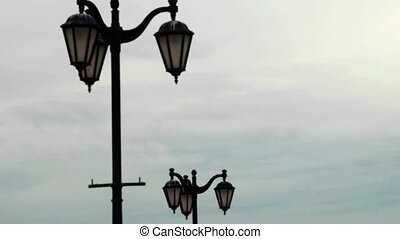Vintage street lamps with running clouds timelapse