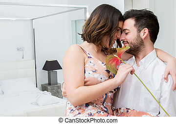 Couple with flower in hotel suite.