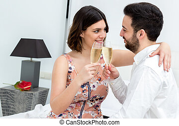 Couple making sparkling wine toast in hotel room.