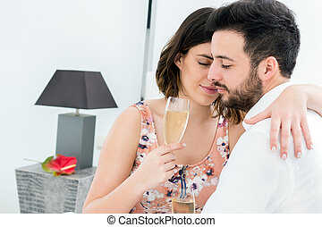 Romantic couple in hotel room with sparkling wine.