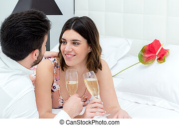 Couple drinking sparkling wine on bed.