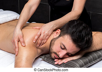 Therapist doing shoulder massage on young man. - Close up of...