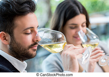 Couple tasting white wine tasting. - Close up portrait of...