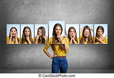 Girl holds and changes her face portraits with different...