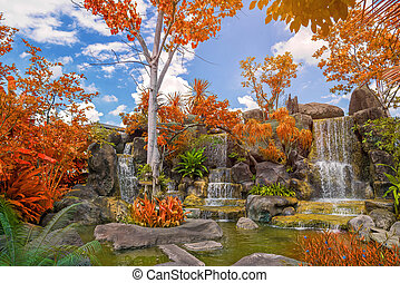 Waterfall in garden at public park with blue sky