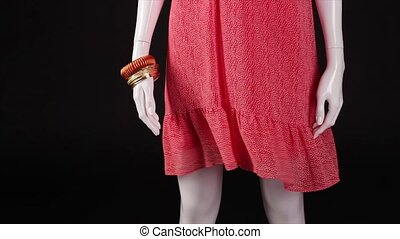 Mannequin in red dress turning. Ripple dress on black...