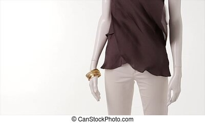 Wind blowing on brown clothes. White pants and brown top....