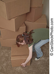 Teenager moving - A teenage girl lifts a box while moving...