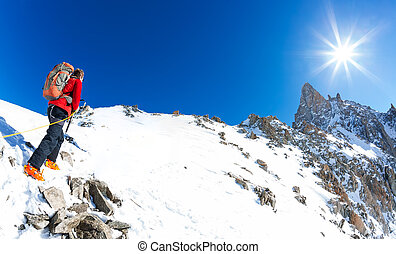 Mountaineer climbs a snowy peak. In background the famous peak Dent du Geant in the Mont Blanc Massif, the highest european mountain.