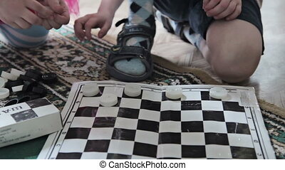 Children play checkers in kindergarden