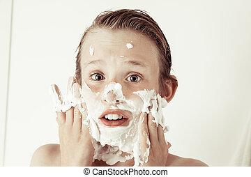 Fun young teenage boy smearing his face with foam - Fun...