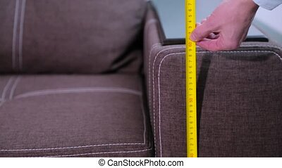 Man measures the dimensions of the furniture