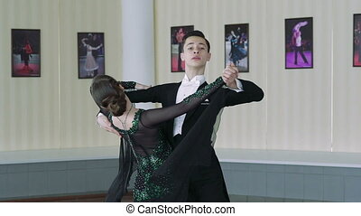 Young couple dancing ballroom dances in classic style. Slow motion