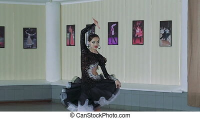 Beautiful young girl performs movements of ballroom dancing...
