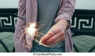 Portrait of a girl looks at camera with sparkler in their...