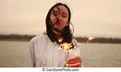 Portrait of young happy woman messy hair holding sparkler in...