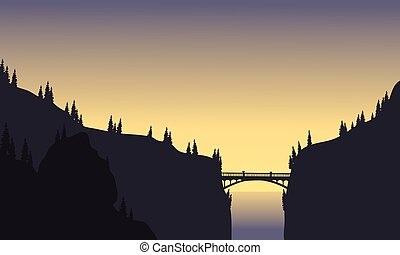 Silhouette of bridge connecting two cliffs at afternoon