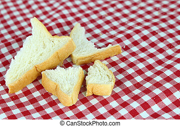 crumb of bread on tablecloth