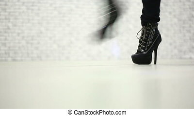 Female legs walking in high heel shoes. many people