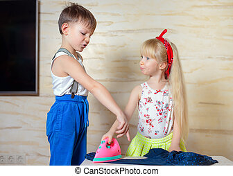 Rough boy pulling iron away from little girl