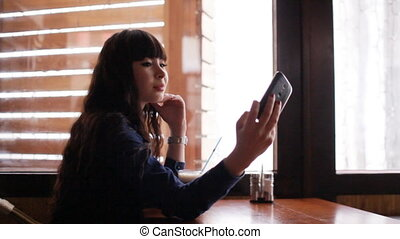 Young girl doing selfie on smartphone in the cafe - Concept:...