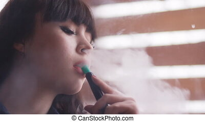 Beautiful young woman inhaling hookah girl smoking shisha in...