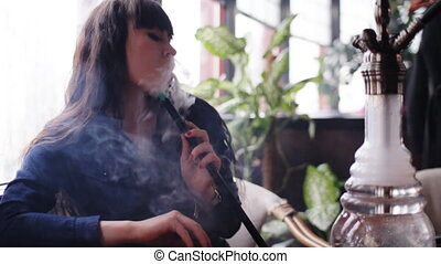 Beautiful young woman inhaling hookah. girl smoking shisha in cafe.