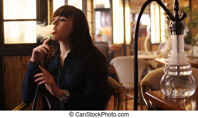 Beautiful young woman inhaling hookah. girl smoking shisha...