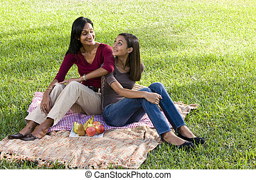 Mother and daughter sitting on picnic blanket - Close mother...