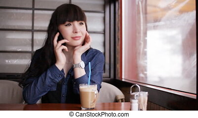 Young girl talking on smartphone in the cafe - Concept:...