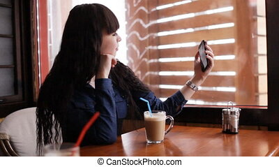 Young girl doing selfie on smartphone in the cafe. Handheld....