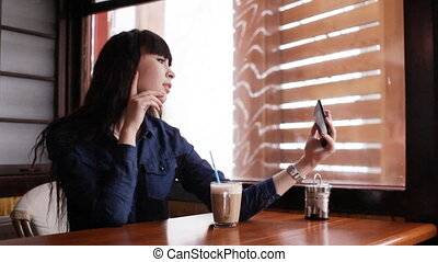 Young girl doing selfie on smartphone in the cafe