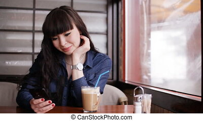 Young girl using smartphone in the cafe - Concept: leisure....
