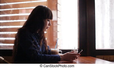 Young girl using smartphone in the cafe - Concept: leisure...