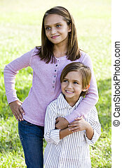 Girl standing with little brother outdoors