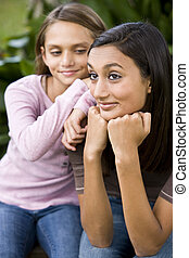 Close-up of teenage girl and younger sister - Close-up of...