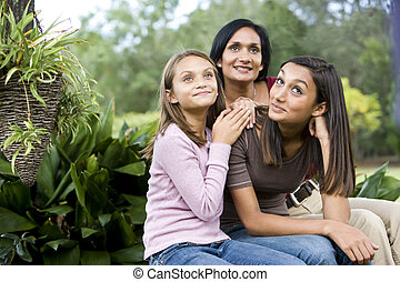 Affectionate mother and two daughters sitting together