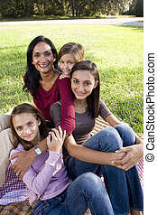 Mother and three children having picnic in park