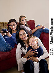 Mother and three children sitting at home together on sofa -...