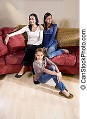 Mother and daughters sitting together at home in living room