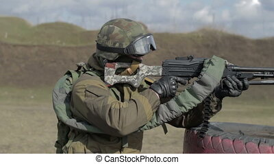 A soldier with a machine gun on a military firing range...