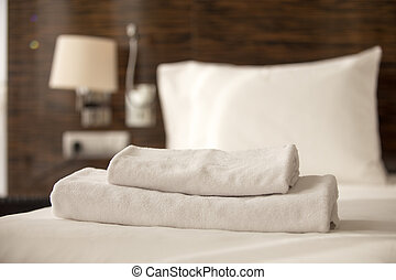 Stack of towels on the bed - Stacked clean white bath towels...