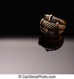 Gold ring on dark glass